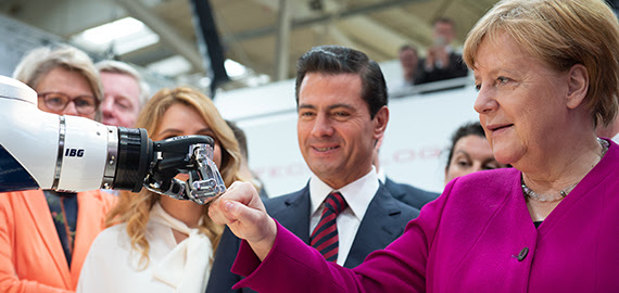 "German Federal Chancellor Angela Merkel and Mexican President Peña Nieto opened Hannover Messe by meeting a prototype home assistant robot built by automation specialist Kuka. The robot, named ""i-do,"" carried coffee and took photos of the two leaders. Merkel and Nieto passed on offering the robot formal handshakes, choosing instead to share a fist-bump with i-do. (Source: Hannover Messe)"